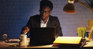 Tired office worker working on the laptop at late night. He yawning and drinking coffee. A businessman is alone in the stock video