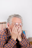 Tired old man. Old man holding hands on eyes under reading glasses royalty free stock photos