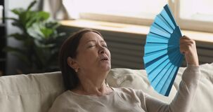 Tired old woman waving fan feel uncomfortable hot at home