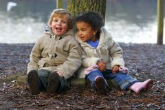 Tired Out Together. A little blond boy and a mixed race girl sitting resting at the base of a tree Royalty Free Stock Image