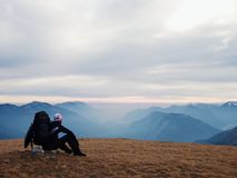 Tired out tourist in black with backpack is sitting on stone in meadow and watching into misty valley. Autumn in mountains. Royalty Free Stock Photography
