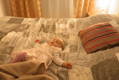 Tired over the day the child is fast asleep on a large bed, with the light of a night Royalty Free Stock Photo