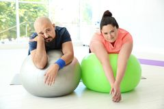 Tired overweight man and woman resting. Tired overweight men and women resting on fitness balls in gym stock photo