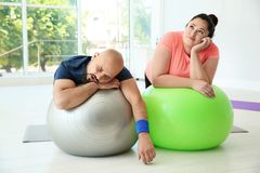 Tired overweight man and woman resting. Tired overweight men and women resting on fitness balls in gym royalty free stock photography