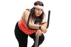 Tired overweight woman on an exercise bike. Isolated on white background Stock Images