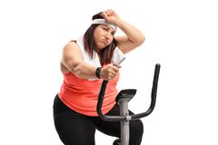 Tired overweight woman exercising on a cross-trainer machine Royalty Free Stock Photo