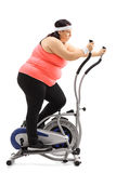 Tired overweight woman exercising on a cross trainer machine Royalty Free Stock Photo