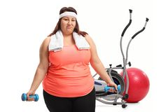 Tired overweight woman exercising with small dumbbells in front. Of exercise equipment isolated on white background Stock Images