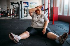 Tired overweight woman sits on the floor in gym. Calories burning, obese female person in sport club, fat people stock photo