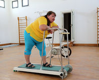 Tired overweight woman on trainer treadmill Stock Photos