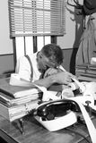 Tired overworked accountant in office, 1950s style Stock Photos