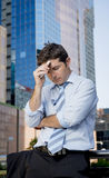 Tired and overworked businessman holding mobile phone worried in stress Royalty Free Stock Images