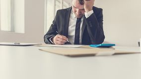 Tired overworked businessman sitting at his desk supporting his head with the arm royalty free stock photos