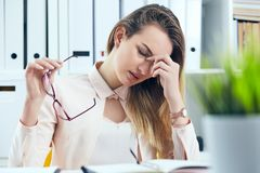 Tired overworked businesswoman in glasses at office covering her face with hand. Tired overworked businesswoman at office covering her face with hands Stock Photo