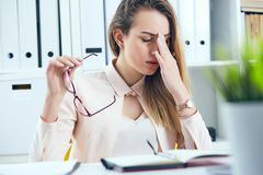 Tired overworked businesswoman in glasses at office covering her face with hand. Tired overworked businesswoman at office covering her face with hands Stock Image