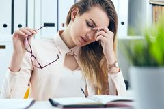 Tired overworked businesswoman in glasses at office covering her face with hand. Tired overworked businesswoman at office covering her face with hands Royalty Free Stock Photography