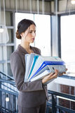 Tired overworked busy businesswoman. Carrying stack of folders with files documents Stock Image