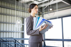 Tired overworked busy businesswoman. Carrying stack of folders with files documents Stock Photography