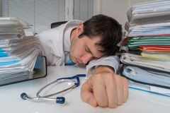 Tired and overworked doctor is sleeping on desk in office.  Stock Images