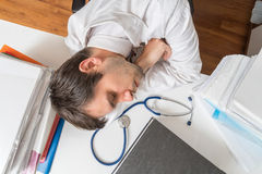 Tired overworked doctor is sleeping on desk in office. View from above.  Stock Photos
