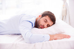 Tired and overworked. Handsome young man in shirt sleeping in bed Royalty Free Stock Images