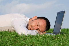 Tired overworked man. Asleep at laptop Stock Image