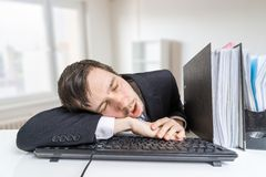 Tired overworked man is sleeping on keyboard in office at work Stock Photo