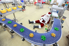 Tired overworked santa claus in factory. Tired overworked santa claus lying on the floor at the  presents production line in factory Royalty Free Stock Photography