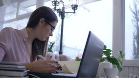 Tired overworked student female into eyeglasses studying with laptop computer with online lesson during distance