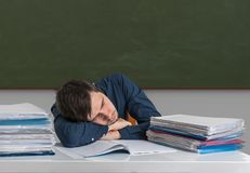 Tired overworked teacher is sleeping on desk in classroom Royalty Free Stock Image
