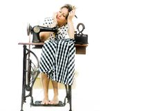 Tired overworked woman dressmaker sleeping by old sewing manual machine - dreaming royalty free stock photo