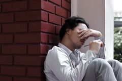 Tired overworked young Asian business man close his eyes and covering face royalty free stock photos