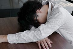 Tired overworked young Asian business man lying with face down on office desk.  Stock Photography