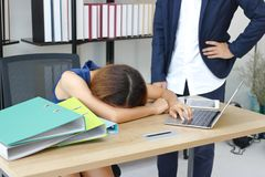 Tired overworked young Asian business woman bend down head on desk against angry boss in office royalty free stock images