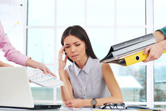 Tired overworked young businesswoman with folders Royalty Free Stock Photos