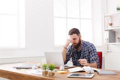 Tired, overworking businessman with laptop in modern white office Royalty Free Stock Photography