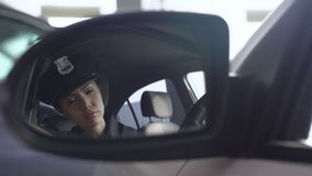 Tired patrolwoman taking off glasses, looking at reflection in rear view mirror stock video