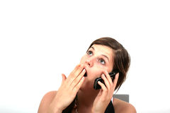 Tired On The Phone. A young woman is yawning on the phone Royalty Free Stock Image