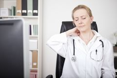 Tired Physician Holding her Nape with Eyes Closed royalty free stock photos