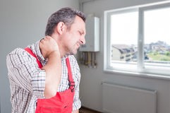 Tired plumber with neck pain. Or injury after a long and stressful day of work with copy space Royalty Free Stock Image