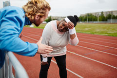 Tired plus-size woman being motivated by personal trainer on running track. Listening to motivation of trainer Royalty Free Stock Photos