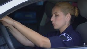Tired police woman leaning on steering wheel, exhausting patrol shift, failure