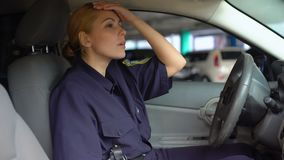 Tired policewoman taking off service cap sitting in patrol car, night shift stock video footage
