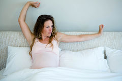 Tired pregnant woman in bed stretching her arms Royalty Free Stock Photos