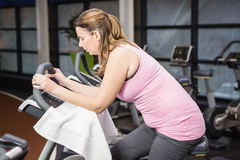 Tired pregnant woman on exercise bike. At the gym Royalty Free Stock Image