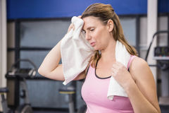 Tired pregnant woman wiping sweat with towel Stock Photo