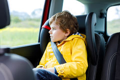 Tired preschool kid boy sitting in car during traffic jam. Sad little school child in safety car seat with belt enjoying trip and jorney. Safe travel with kids royalty free stock images