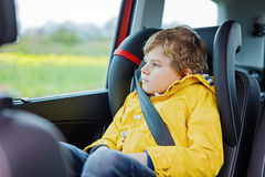 Tired preschool kid boy sitting in car during traffic jam. Sad little school child in safety car seat with belt enjoying trip and jorney. Safe travel with kids royalty free stock image