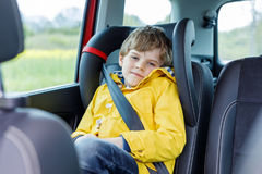 Tired preschool kid boy sitting in car during traffic jam. Sad little school child in safety car seat with belt enjoying trip and jorney. Safe travel with kids stock image