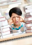 Tired pretty girl surrounded with books. Tired pretty girl with headache surrounded with piles of books Royalty Free Stock Image